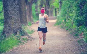 Mujer deportiva atlética trotando al aire libre en la naturaleza,