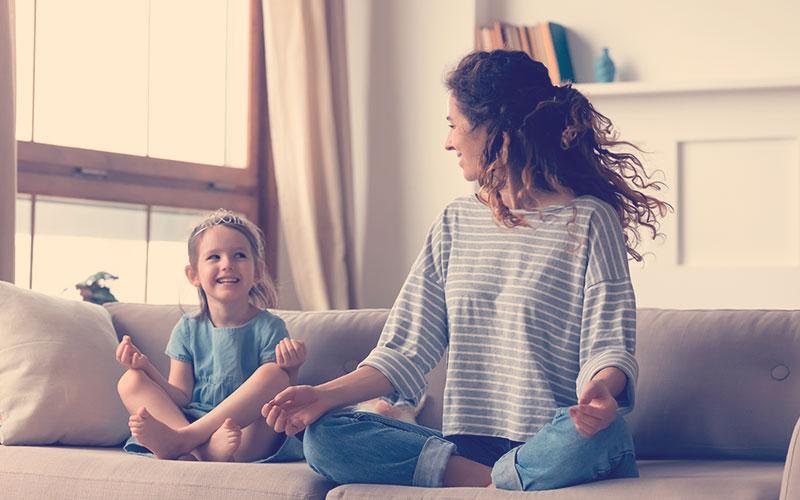 Niña pequeña linda con diadem de princesa y madre joven sentada en loto