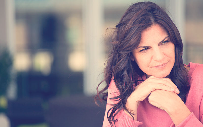 Mujer cruzada de manos mientras piensa sobre los síntomas de la premenopausia