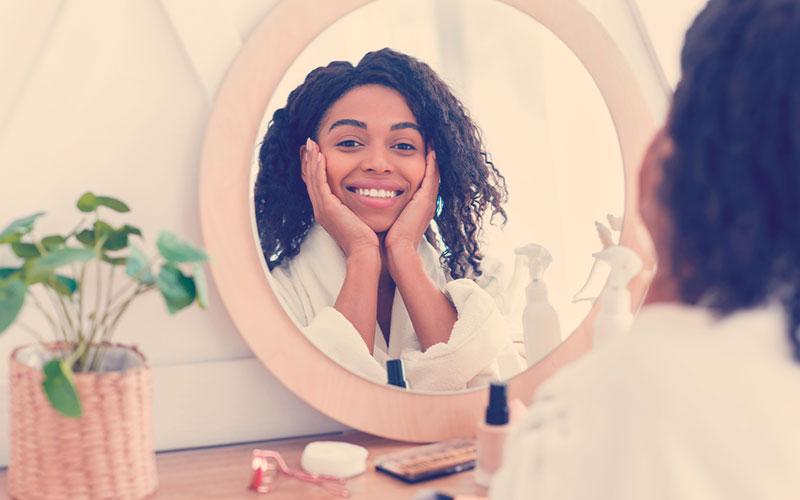 mujer mirándose al espejo mientras sonríe