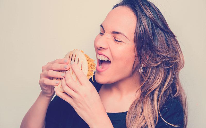 Niña latina sostiene una arepa en sus manos lista para comerla, Arepa rellena de pollo