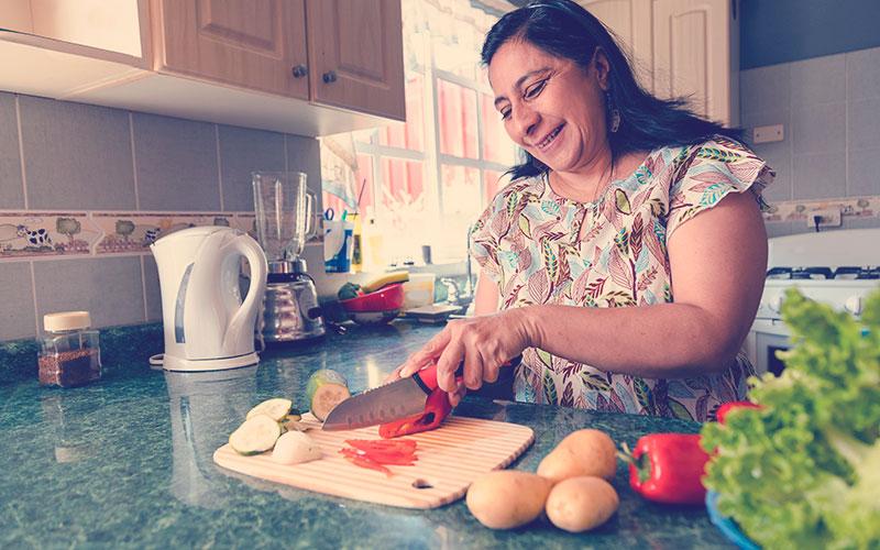 Mamá colombiana feliz cocinando comida saludable