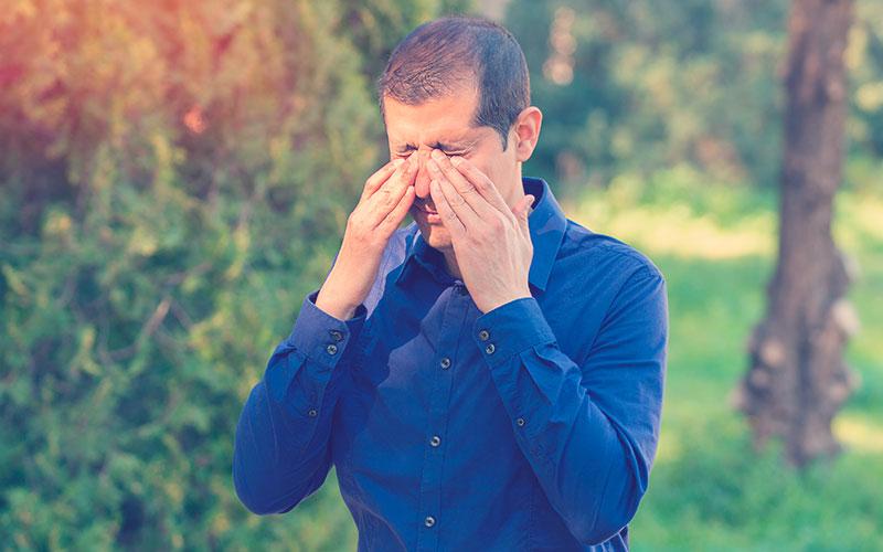 Hombre cubriendo los ojos a mano de luz solar brillante