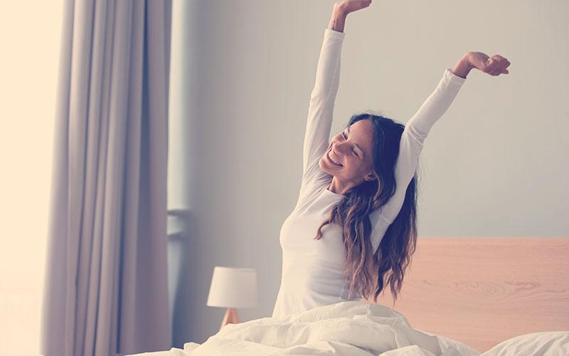 Una mujer feliz con ropa de noche sentada en la cama despertando despues de un sueño reparador