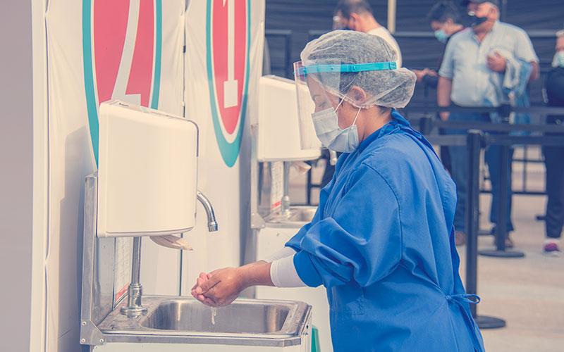 Enfermera lavándose manos en un punto vacunación Compensar