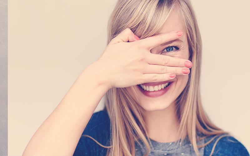 Mujer sonriendo mientras tapa uno de sus ojos