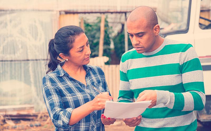 Mujer y hombre latinoamericano parados afuera cerca del auto en segundo plano con invernadero de granjas, discutiendo documentos