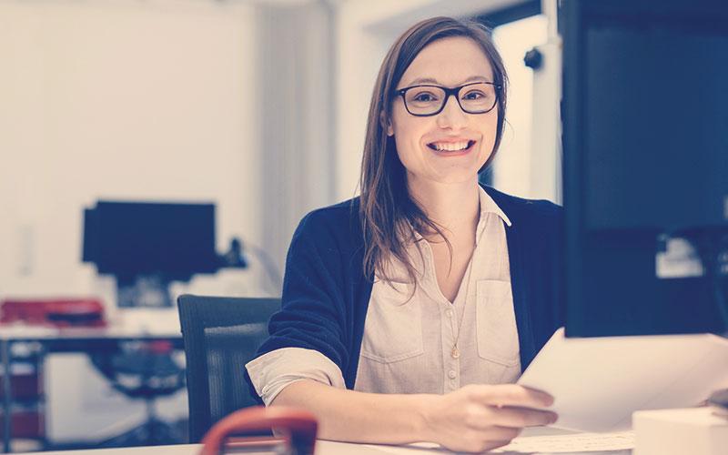 colaboradora de una empresa sonriendo en su puesto de trabajo