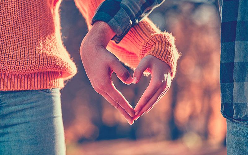 Manos de una pareja formando un corazón