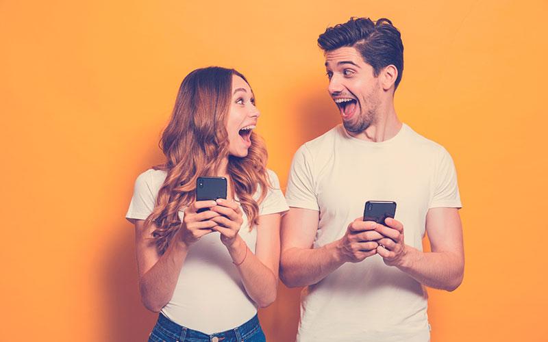Foto de gente positiva y emocionada, hombre y mujer gritando y mirándose mientras ambos usan teléfonos móviles aislados sobre fondo amarillo