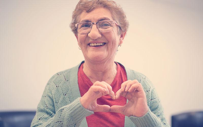 Persona mayor realizando un corazón con sus manos
