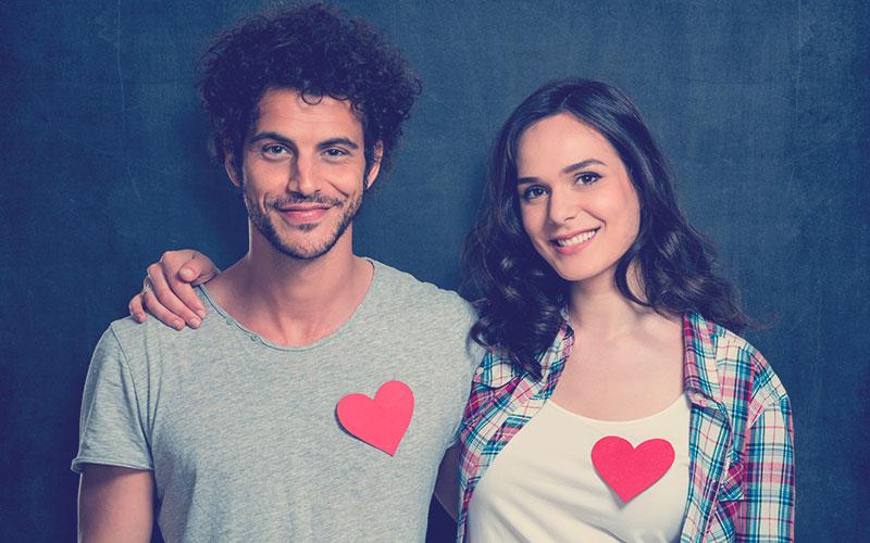 Joven pareja feliz con forma de corazón rojo