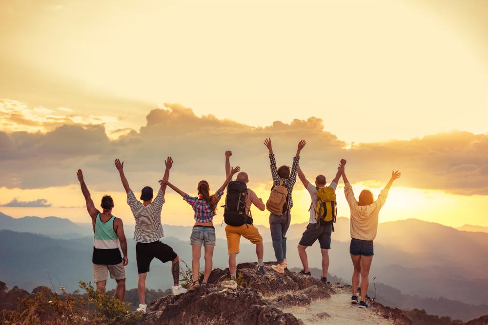 Grupo de amigos felices levantados con los brazos levantados en la montaña al atardecer