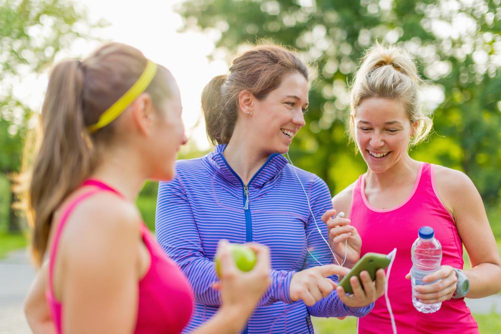 Grupo de chicas activas felices preparándose para una carrera en la naturaleza eligiendo música en un teléfono inteligente