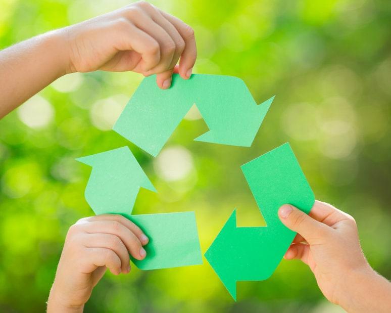 Manos de niños sostienen papel reciclable