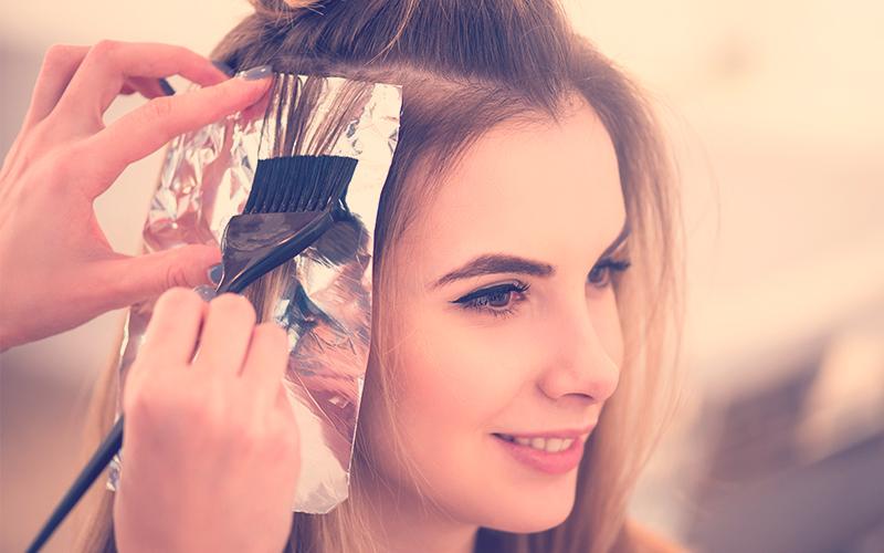 Peluquería profesional teñiéndose el pelo de su cliente