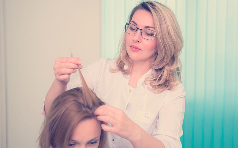 Un tricólogo examina el pelo de una mujer