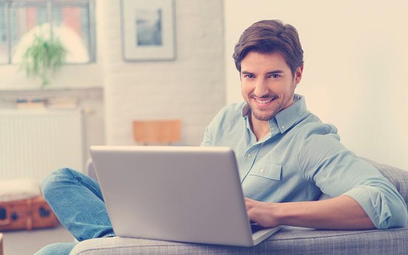 Simpático joven relajándose en casa con un ordenador portátil
